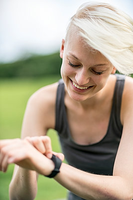 Smiling young woman checking her smartwatch - p300m1205127 by A. Tamboly