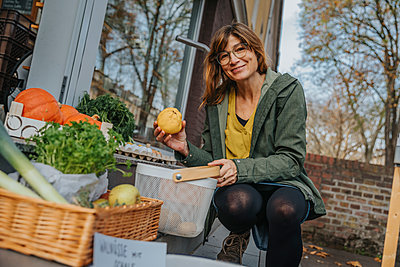 Costumer putting vegetables into basket at organic food store, Cologne, NRW, Germany - p300m2256200 von Mareen Fischinger