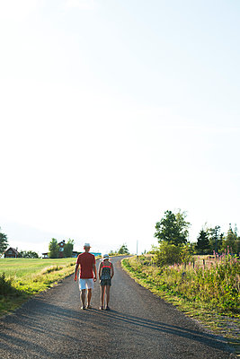 Father and daughter walking along rural road in Smaland, Sweden - p352m2039816 by Julia Sjöberg