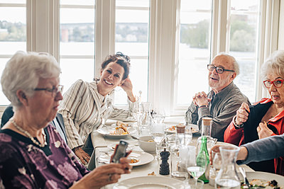 Senior friends talking while sitting in restaurant - p426m2149125 by Maskot