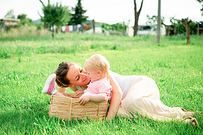Mother lying on grass gazing at toddler daughter, Arezzo, Tuscany, Italy - p429m2098232 by Senserini Lucrezia
