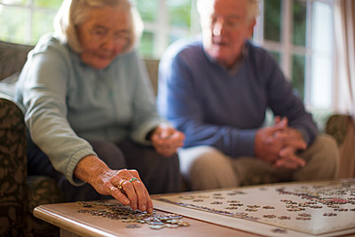 Older couple on sofa solving jigsaw puzzle - p555m1305746 by Resolution Productions
