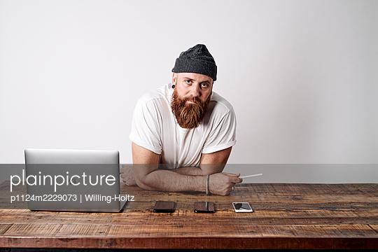 Mann am Schreibtisch mit Laptop und Smartphones - p1124m2229073 von Willing-Holtz