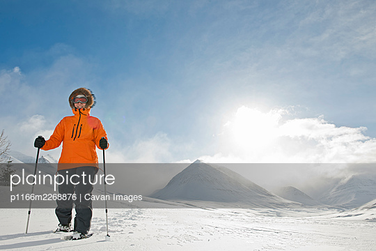 woman walking on snowshoes through winter landscape in Iceland - p1166m2268876 by Cavan Images