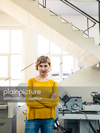 Mature businesswoman with arms crossed standing in factory - p300m2282112 by Joseffson