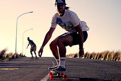 A young man skateboarding on a road. - p1100m1482344 by Mint Images