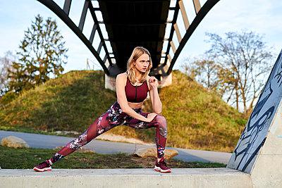 Young woman stretching, Lake Phönixsee, Dortmund - p890m2231031 by Mielek