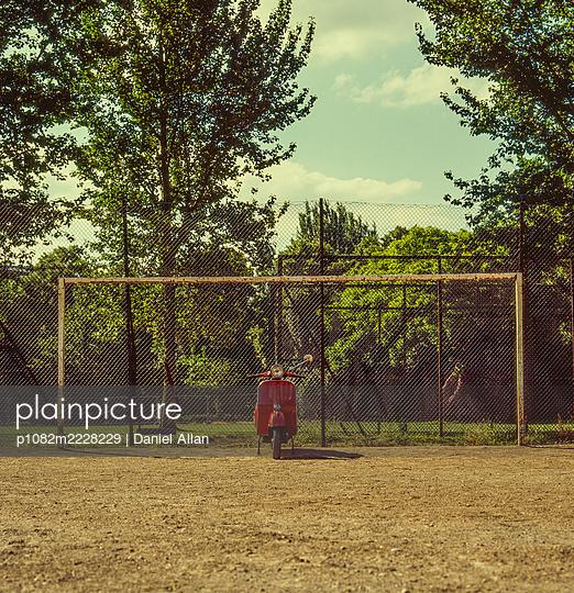 Rote Vespa vor einem Fußballtor - p1082m2228229 von Daniel Allan