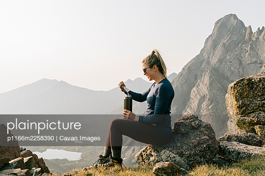 Side view of woman having energy drink while sitting on mountain against clear sky - p1166m2258390 by Cavan Images