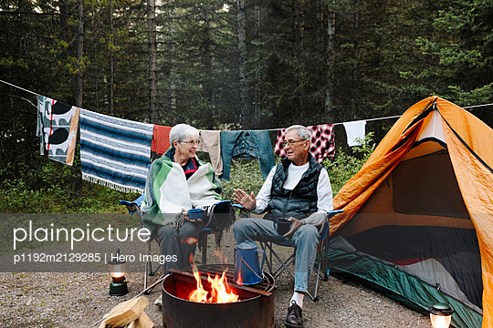 Senior couple relaxing and talking at campsite campfire - p1192m2129285 by Hero Images