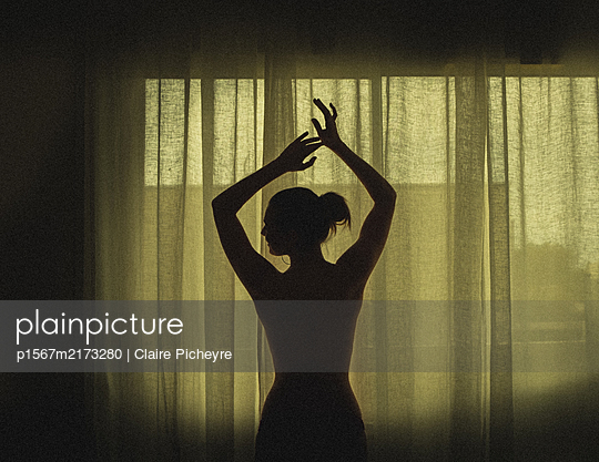 Silhouette of a woman in front of a curtain - p1567m2173280 by Claire Picheyre