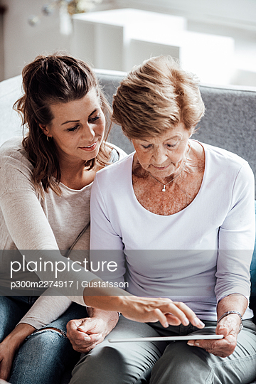 Young woman using digital tablet held by grandmother on sofa - p300m2274917 by Gustafsson