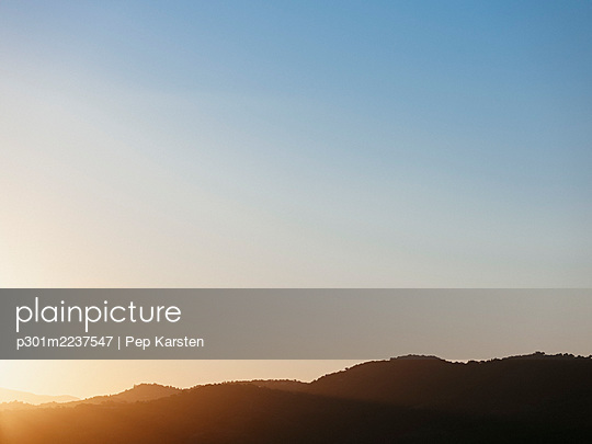 Tranquil blue sunset sky over silhouetted hills, Tanneron, French Riviera, France - p301m2237547 by Pep Karsten