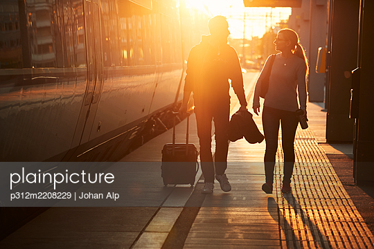 Couple at train station platform - p312m2208229 by Johan Alp