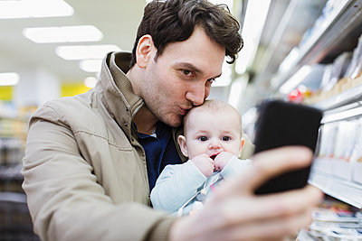 Affectionate father and baby daughter taking selfie in supermarket - p1023m2187671 by Sam Edwards
