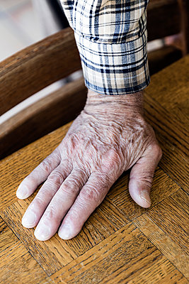 Cropped hand of senior man on wooden table - p1094m1467644 by Patrick Strattner