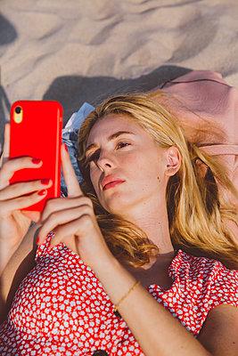 Attraktive junge Frau am Strand mit Handy - p432m2149890 von mia takahara