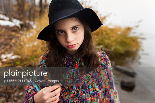Portrait of girl wearing hat and colorful poncho while standing by lake - p1166m2111946 by Cavan Images