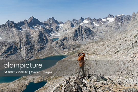 Rear view of man photographing mountains while hiking during vacation - p1166m2258416 by Cavan Images