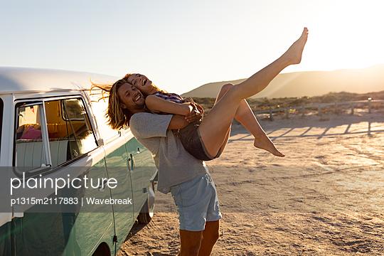 Man holding woman near camper van at beach - p1315m2117883 by Wavebreak