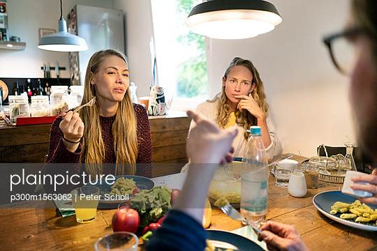 Friends eating pasta at wooden table - p300m1563062 by Peter Scholl