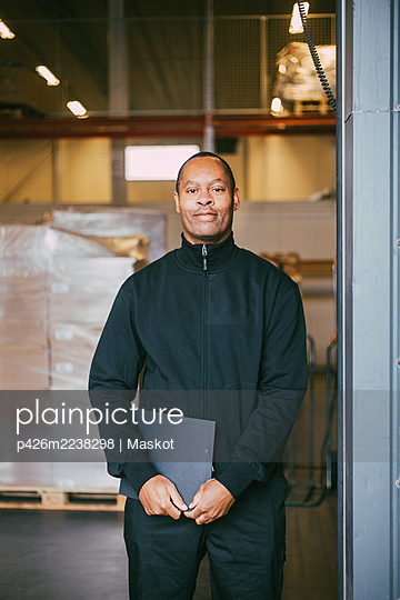 Portrait of smiling male manual worker at warehouse - p426m2238298 by Maskot