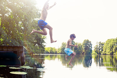 Father and son jumping into lake - p1023m987055f by Tom Merton