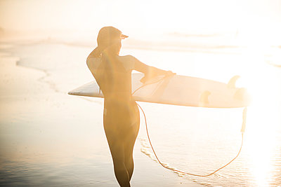 Independent Asian Woman looking out for sunrise summer surf at beach - p1166m2279617 by Cavan Images