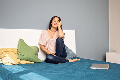 Brunette woman sits on bed relaxing  - p294m2132902 by Paolo
