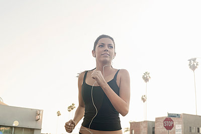 Confident woman jogging while listening music against clear sky - p300m2240007 by LOUIS CHRISTIAN