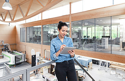 Businesswoman using digital tablet while leaning on railing in factory - p300m2265193 by Florian Küttler