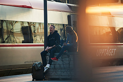 Couple waiting at train station platform - p312m2208223 by Johan Alp