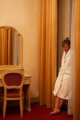 Nachdenkliche Frau im Bademantel lehnt sich an Wand - p795m2087459 von JanJasperKlein