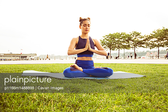 Woman sitting in prayer position while mediating on grassy field at park