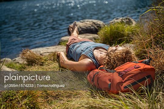 Junger Mann macht eine Pause beim Wandern - p1355m1574233 von Tomasrodriguez
