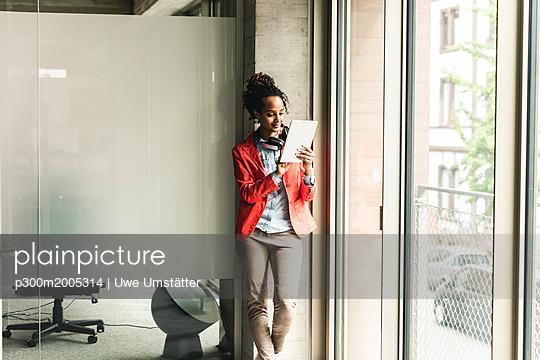 Young woman with headphones standing in corridor, using digital tablet - p300m2005314 von Uwe Umstätter