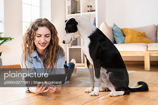Smiling woman looking at digital tablet while lying on hardwood floor by Jack Russell Terrier in living room - p300m2277561 by Steve Brookland
