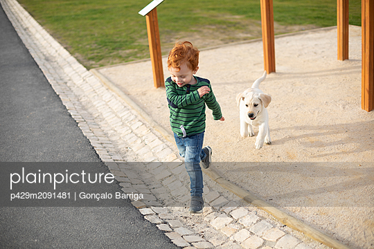 Boy running away from pet puppy - p429m2091481 by Gonçalo Barriga