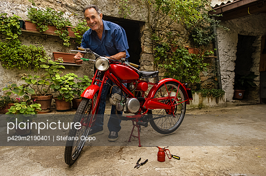Mature man standing in courtyard, fixing red vintage motorcycle. - p429m2190401 by Stefano Oppo