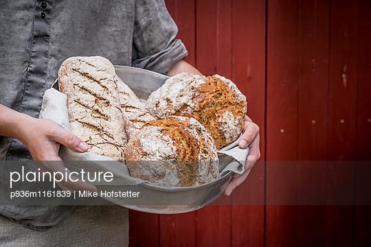 Frisches Brot in einer Kuchenform - p936m1161839 von Mike Hofstetter