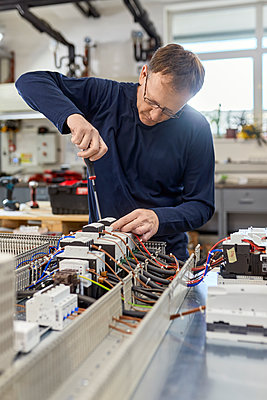 Electrician working on circuitry in workshop - p300m2180832 by Zeljko Dangubic