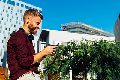 Mid adult businessman with headphones using smart phone while sitting in city - p300m2250829 by Boy photography