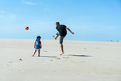 Geschwister spielen Fußball am Strand - p427m1462745 von R. Mohr