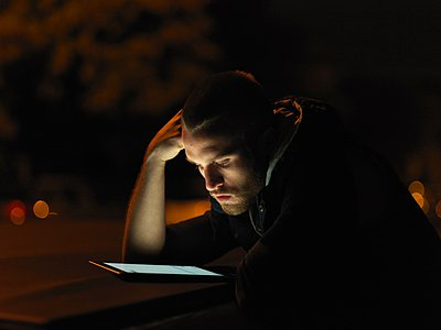 Young man using digital tablet, outdoors, at night, face illuminated - p429m1052750 by Elke Meitzel