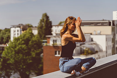 Junge Frau macht Yogaübung auf Hausdach - p432m2231515 von mia takahara