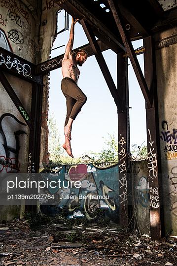 Mann hält sich an einem Holzbalken fest - p1139m2027764 von Julien Benhamou