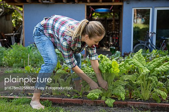 Blonde woman in her garden - p1678m2258835 by vey Fotoproduction
