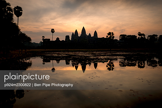 Cambodia, Siem Reap, Silhouette of Angkor Wat seen across water at sunrise - p924m2300822 by Ben Pipe Photography