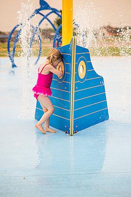 Full length of girl in swimwear enjoying at water park - p1166m1473762 by Cavan Images