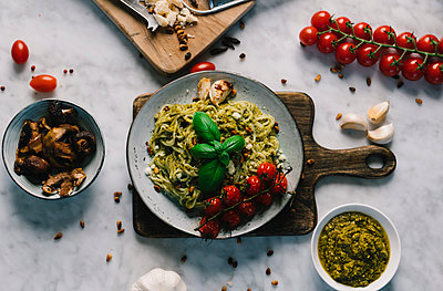 Overhead view of cooked spaghetti in plate with ingredients on table - p1166m2025166 by Cavan Images